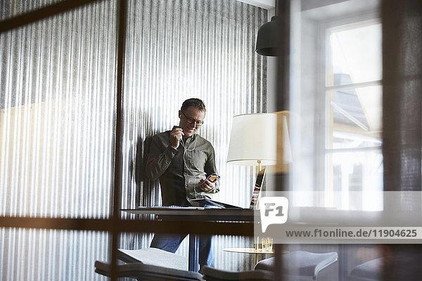 Der reife Geschäftsmann spricht mit dem Smartphone über Kopfhörer aus dem Glas im Kreativbüro.