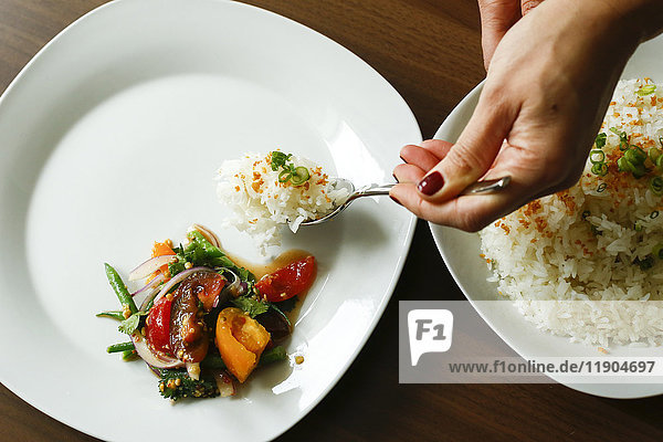 Hands of woman serving rice