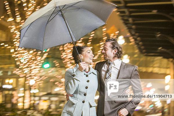 Caucasian couple carrying umbrella in city at night