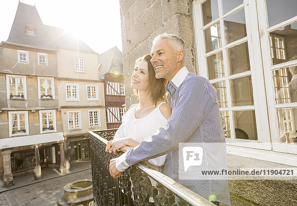 Caucasian couple smiling on balcony in city