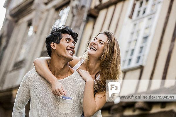 Man carrying woman piggyback in city
