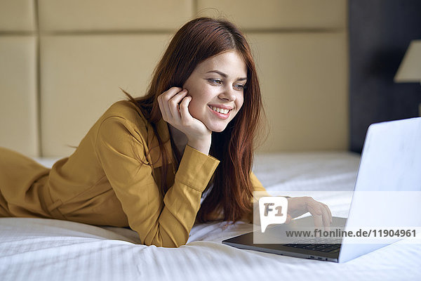 Smiling Caucasian woman laying on bed using laptop
