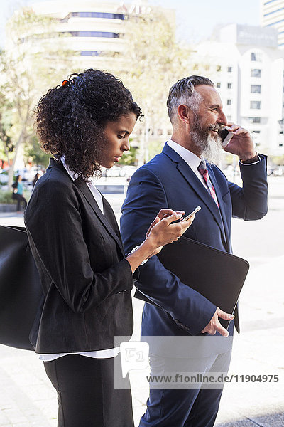 Business people using cell phones outdoors