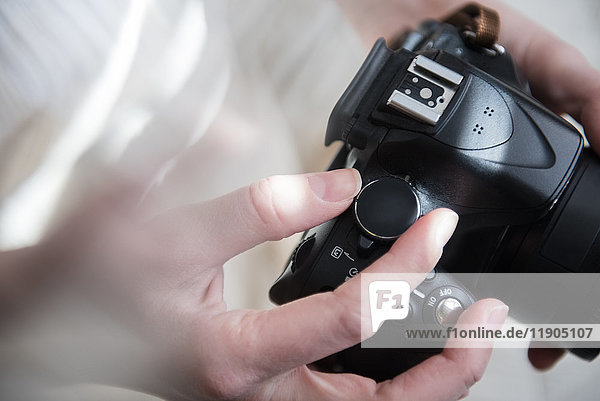 Hands of Caucasian woman turning dial on camera