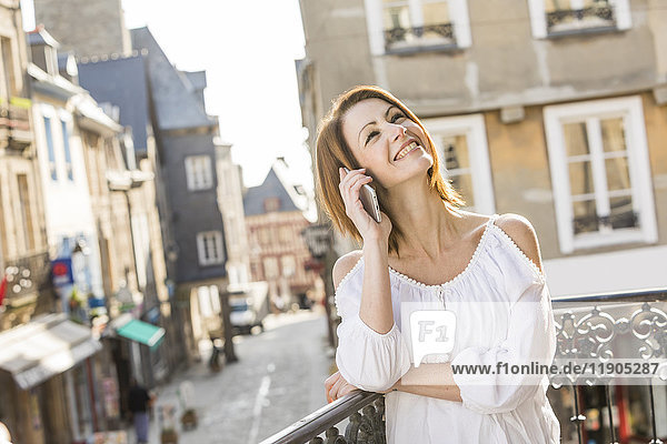Caucasian woman talking on telephone in city