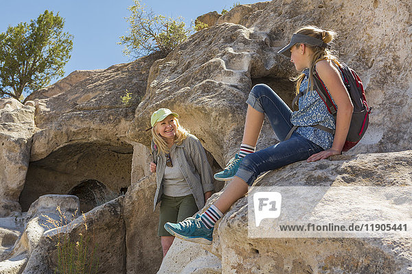 Portrait of Caucasian grandmother and granddaughter playing on rock