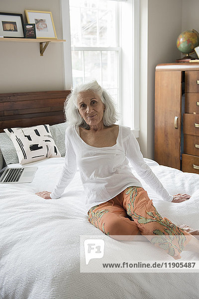 Portrait of smiling older woman sitting on bed