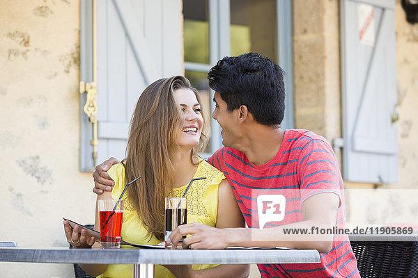 Couple reading menu and hugging at restaurant