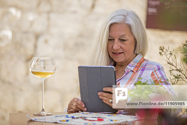Older Caucasian woman drinking white wine and using digital tablet
