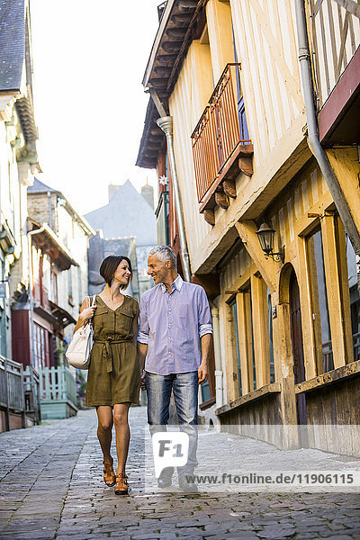 Caucasian couple holding hands walking in city