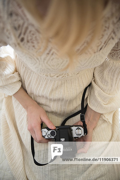 Hands of Caucasian woman holding camera in lap