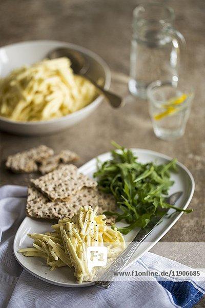 Sellerie-Remoulade mit Rucola  Knäckebrot und einem Glas Zitronenwasser