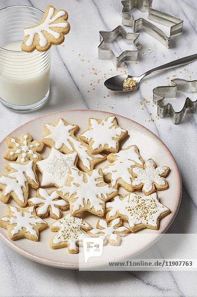 Butterplätzchen  weihnachtlich mit Zuckerglasur verziert  mit Milchglas und Ausstechförmchen