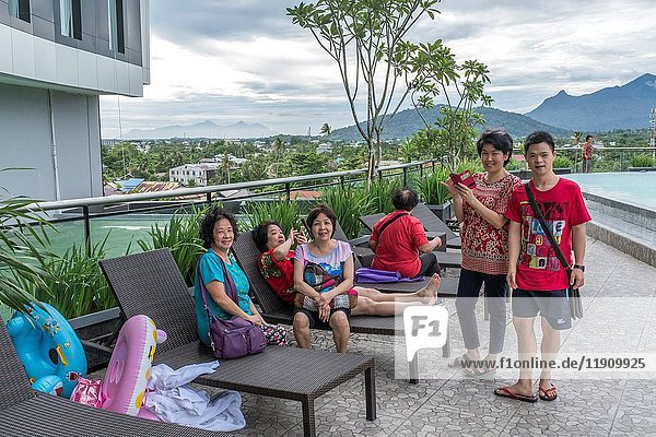 Group of friends relaxing at poolside  Swiss-Belinn Hotel  Singkawang  West Kalimantan  Indonesia