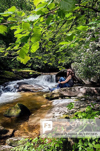 Young woman sitting by Davidson River in Pisgah National Forest - near Brevard  North Carolina  USA.