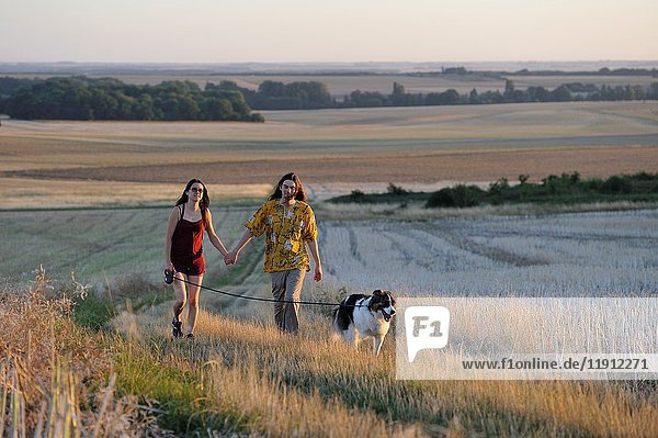 Couple of young people walking with a dog around Mittainville  Yvelines department  Ile-de-France region  France  Europe.