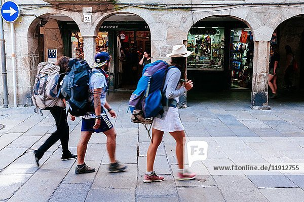 Pilgrims walking down a typical pedestrian cobbled street in old town.