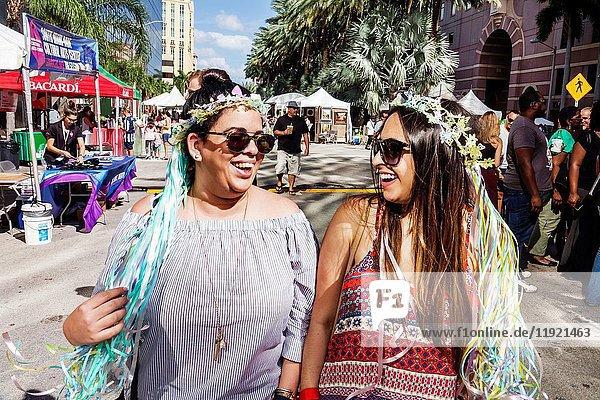 Florida  Coral Gables  Miami  Carnaval Miami  carnival  street festival  Latin cultural celebration  woman  women  Hispanic  friends  walking  strolling  girlfriends  laughing  floral head wreath