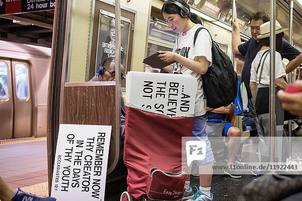 An Asian Evangelical church member travels on the subway in New York with her signs