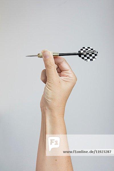 Hand holding darts.