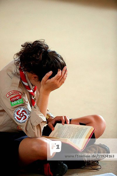 Girl scout reading a book.