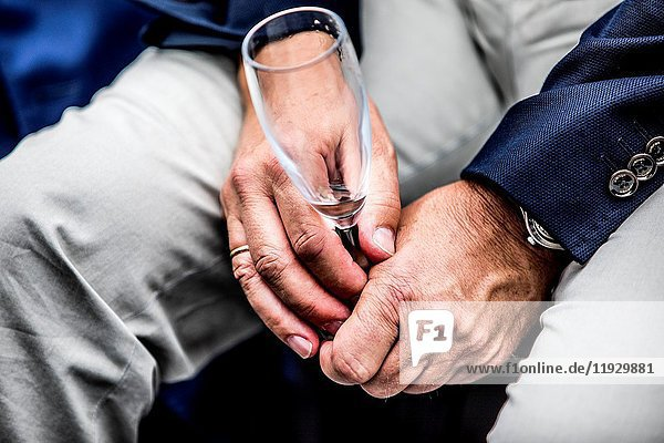 Close-up of male hands with empty champagne flute.