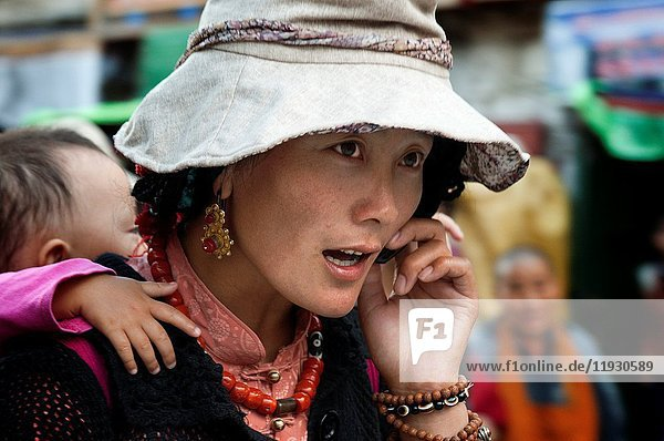 A woman carrying her son on the streets of Lhasa. Bakhor square  Lhasa  Tibet.