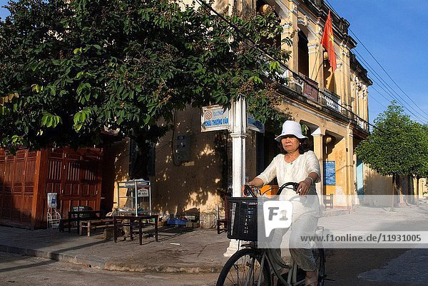 Vietnam  Quang Nam Province  Hoi An  Old Town  listed as World Heritage by UNESCO  traditional house. Bach Dang street. Vietnam. A woman on bicycle..