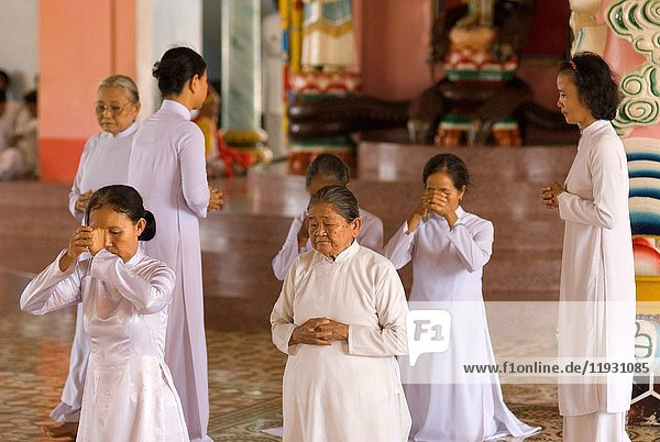 Worshipers at midday prayer in the Cao Dai temple  Tay Ninh  Vietnam  Asia.