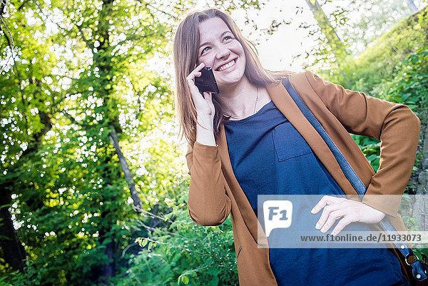 A young woman talking on cell phone outdoors.