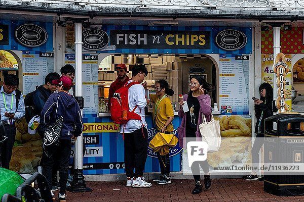 A group of young Chinese tourists buying fish and chips in the rain on Brighton seafront  Brighton  East Sussex  UK.