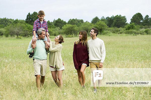 Familie geht gemeinsam durchs Feld