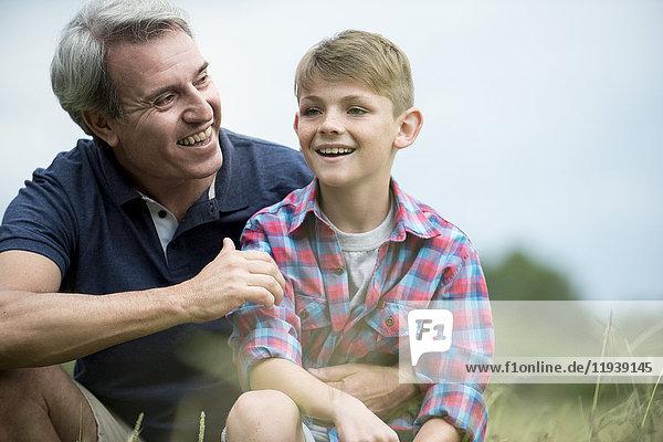 Vater und Sohn lachen gemeinsam im Freien.