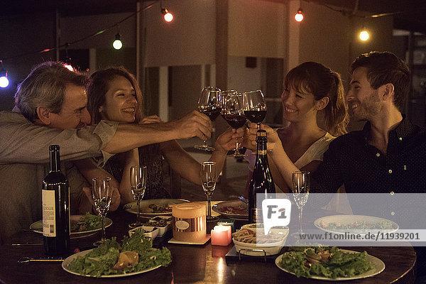 Freunde klirren auf der Dinnerparty mit Weingläsern.