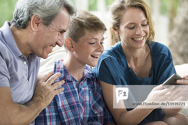 Familie betrachtet Smartphone zusammen