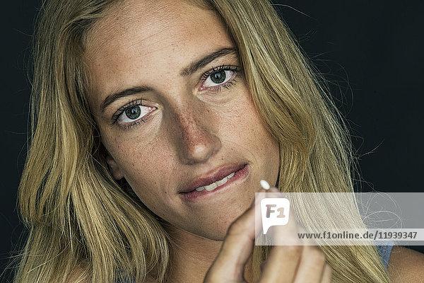 Junge Frau mit Pille und beißenden Lippen