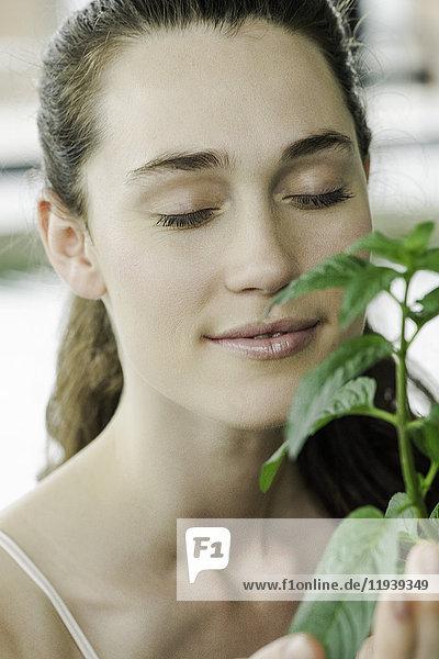 Junge Frau riecht Pflanze