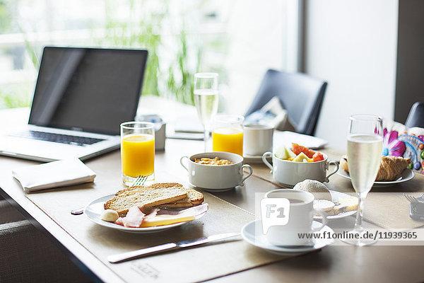 Frühstück auf dem Tisch neben dem Laptop-Computer
