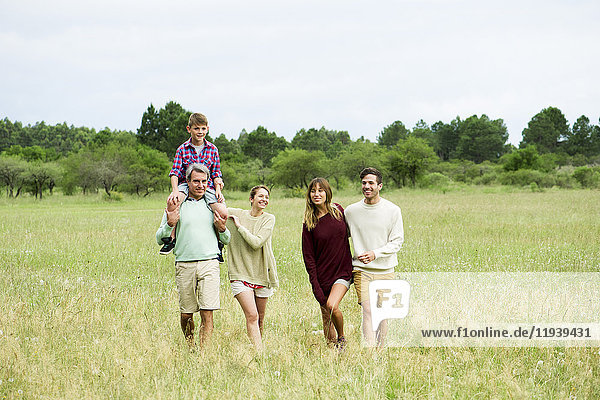 Family walking together through field