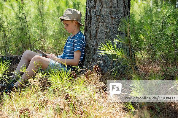 Junge mit digitalem Tablett im Wald