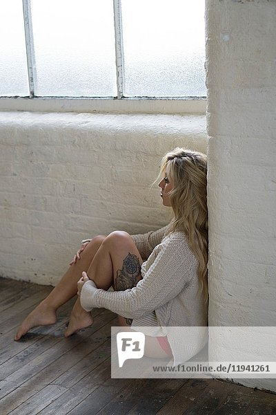 Lonely young blond woman sitting on the floor by the window looking away.