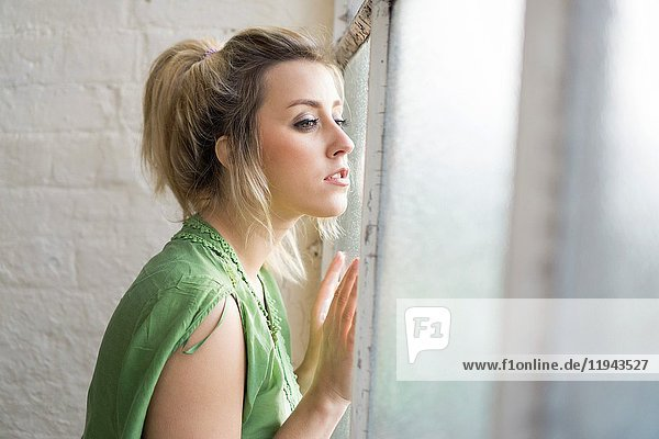 Beautiful young woman looking out of the window.