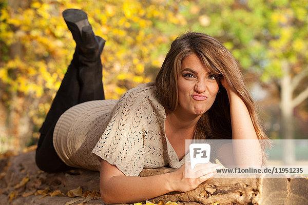 Liegende junge Frau im Freien im Herbst und verzieht den Mund