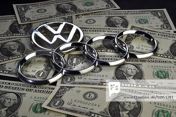 Audi und VW-Emblem auf Dollarscheinen