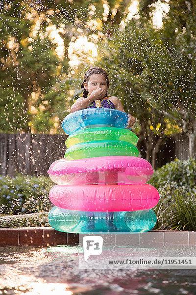 Junges Mädchen  das inmitten von aufblasbaren Ringen an der Seite eines Freibads steht