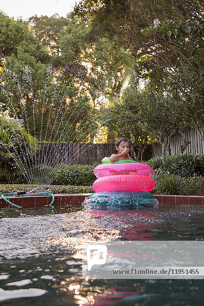 Young girl  standing in the middle of inflatable rings in outdoor swimming pool