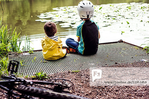 Two young brothers sitting at water's edge  rear view