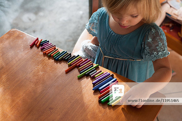 Girl lining up crayons in a row