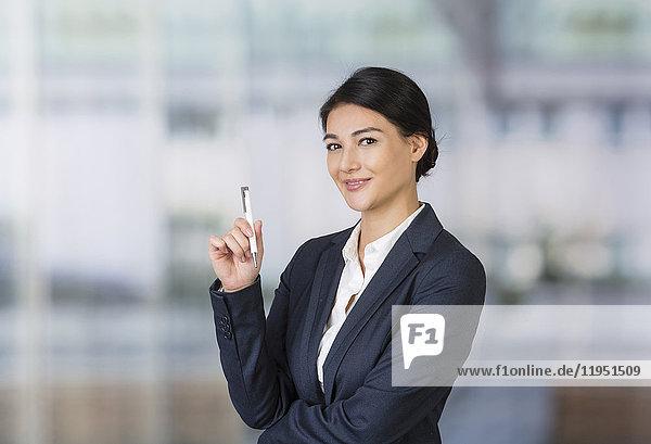 Portrait einer lächelnden Geschäftsfrau mit Kugelschreiber
