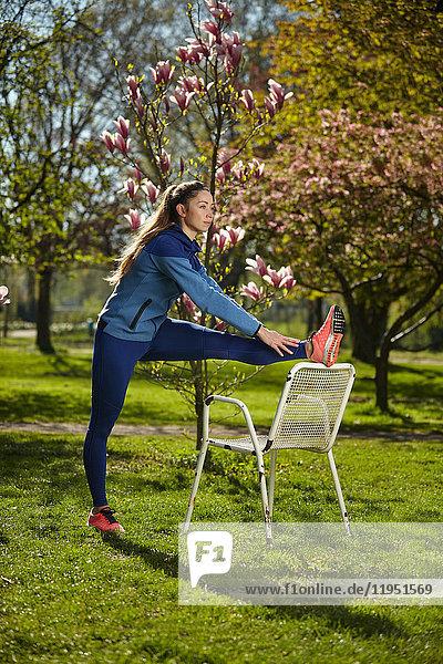 Sportliche Frau dehnt sich in einem Park im Frühling